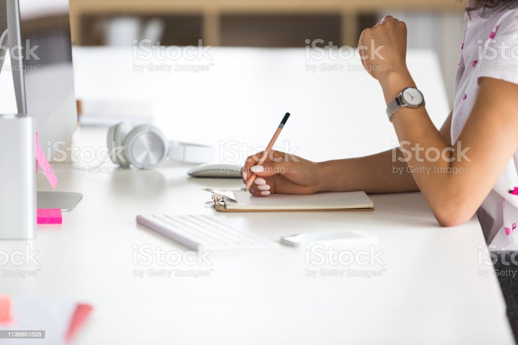 Woman making notes at office desk Close up of female hands writing on notepad while working at her desk. Focus on female hands holding pencil making notes while working in office. Adult Stock Photo