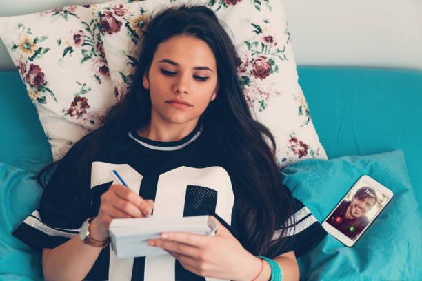 woman making notes in bed - compagni scuola foto e immagini stock