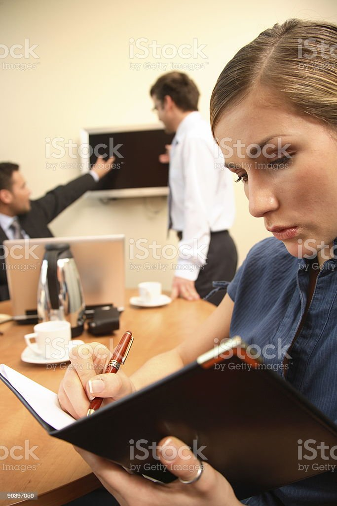 woman making notes. Men are talking about data on screen - Royalty-free Adult Stock Photo