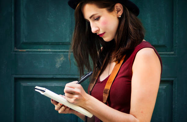 Woman Making Notes Outside City Concept stock photo