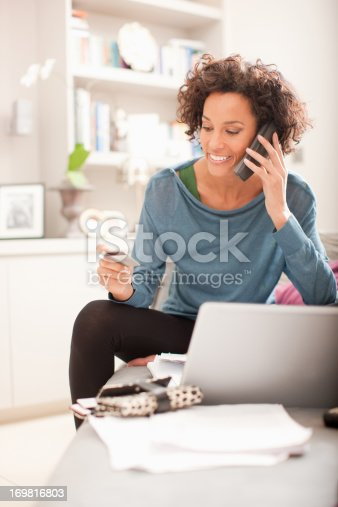 istock Woman making online purchase and talking on cellphone 169816803