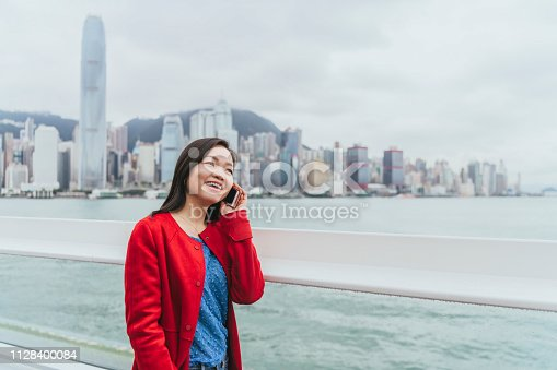 Cheerful Chinese woman smiling and talking on phone, walking along city bay