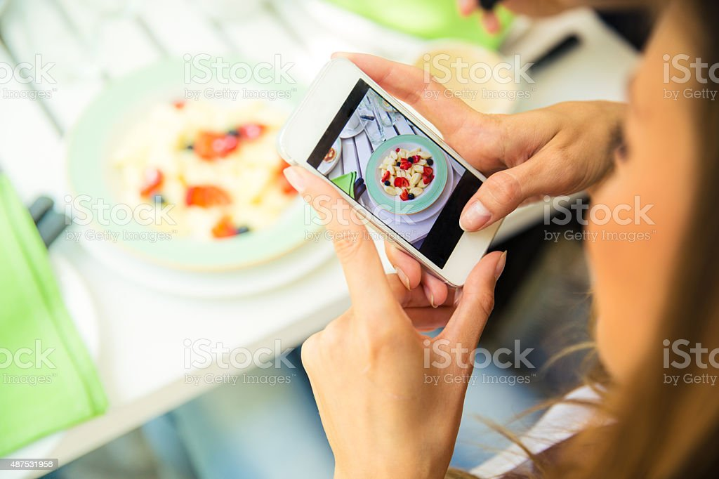Woman making photo of food on smartphone stock photo