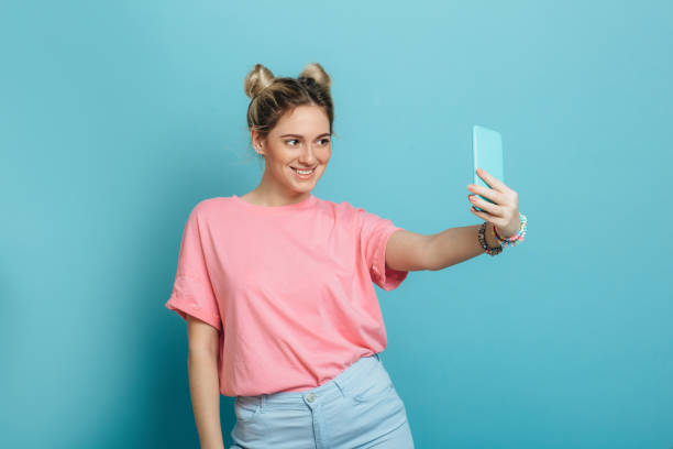 woman making photo on her smartphone on blue background - selfie foto e immagini stock