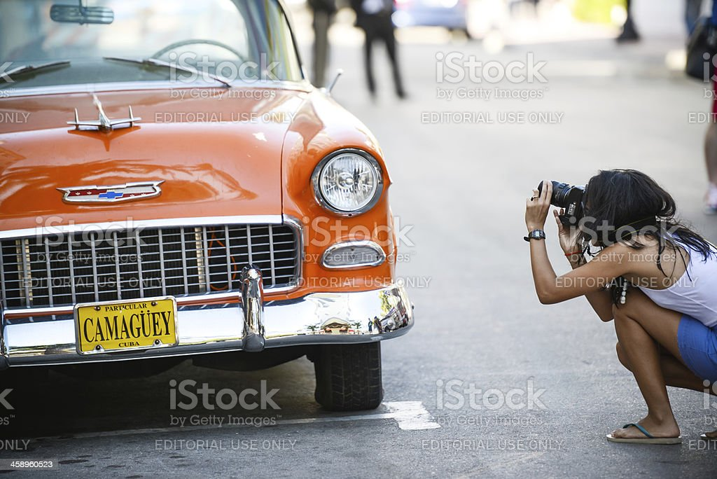 Woman making photos of old Chevy parked on street royalty-free stock photo