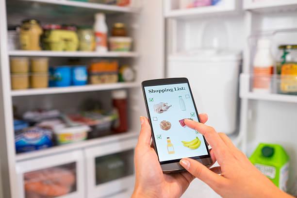 Frau macht Einkaufen Liste auf Telefon mit dem Kühlschrank. – Foto