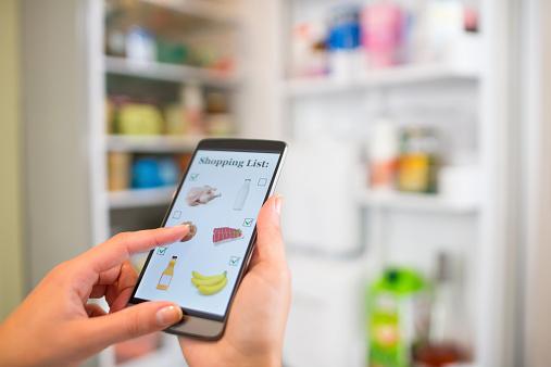 Mujer Haciendo Lista De Compras En El Teléfono Conectado Con El Refrigerador Foto de stock y más banco de imágenes de Adulto