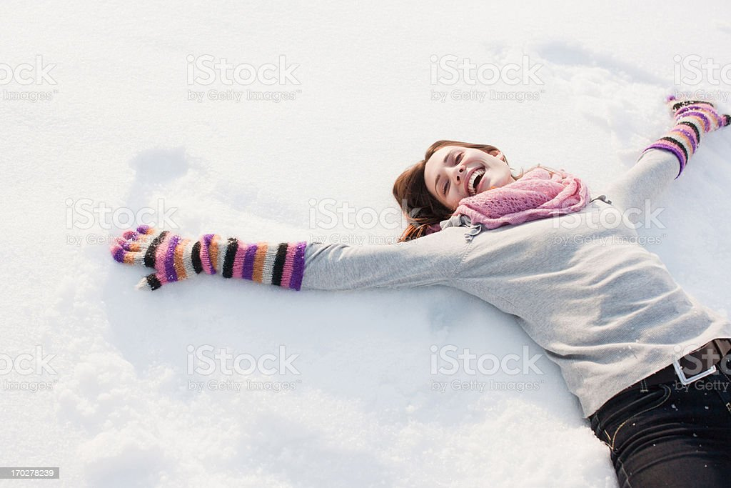 Woman making snow angel stock photo