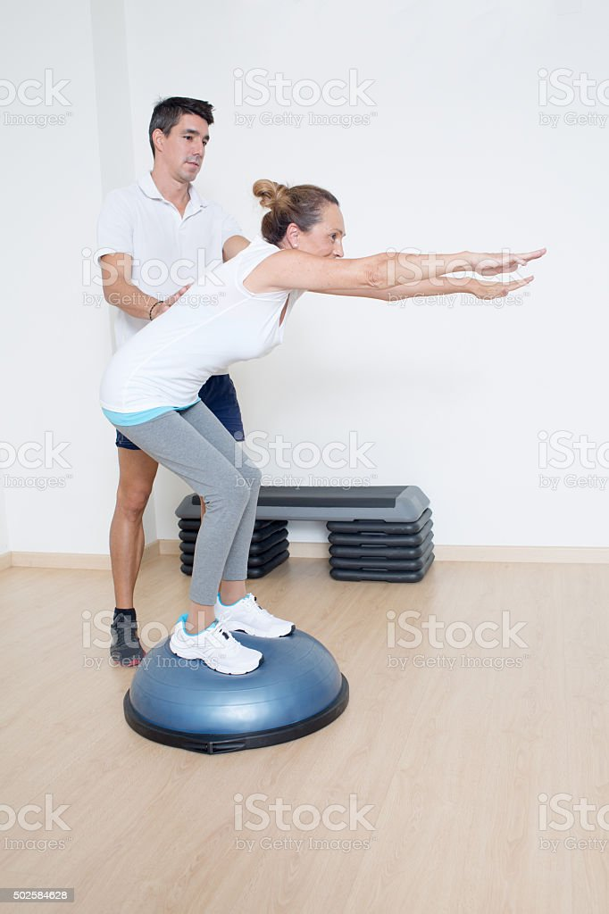 Woman making squats on balance trainer stock photo