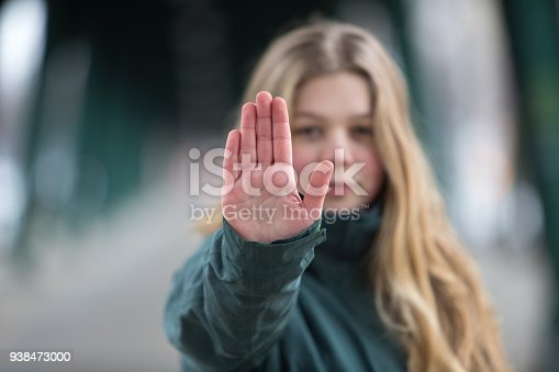 attractive young woman with blond hair and serious face making stop gesture with her hand.