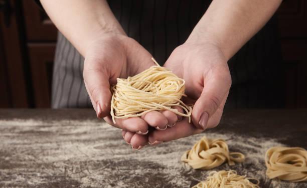 frau macht tagliatelle-nest am küchentisch - italienische küchen dekor stock-fotos und bilder