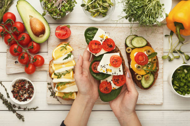 Woman making tasty bruschettas for healthy snack, top view Female hands holding bruschetta with cheese, basil and tomato. Healthy vegetarian sandwiches at kitchen table with various vegetables bowls and greens. Cooking food background, top view female sandwich stock pictures, royalty-free photos & images