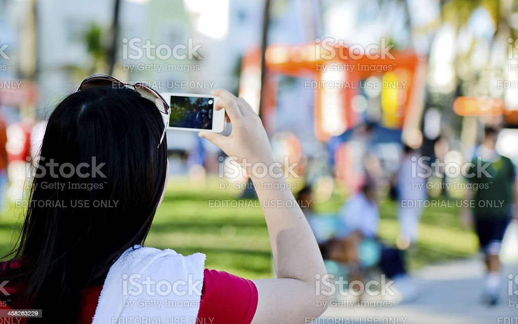 Woman making video with iPhone on Ocean Drive, Miami Beach royalty-free stock photo