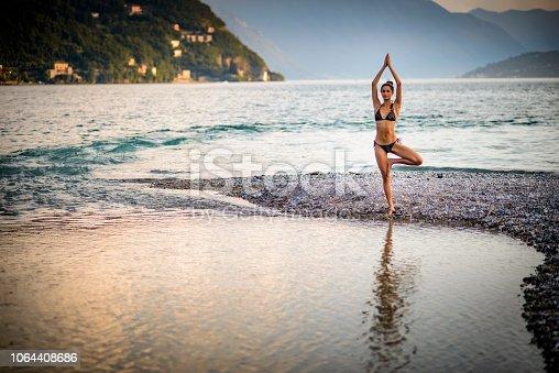 Woman in bikini making yoga by the lake.