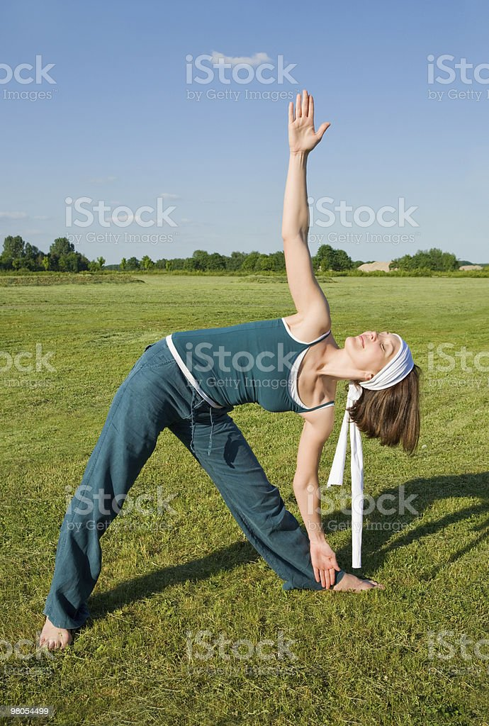Woman making Yoga exercises in top of a stone wall royalty-free stock photo
