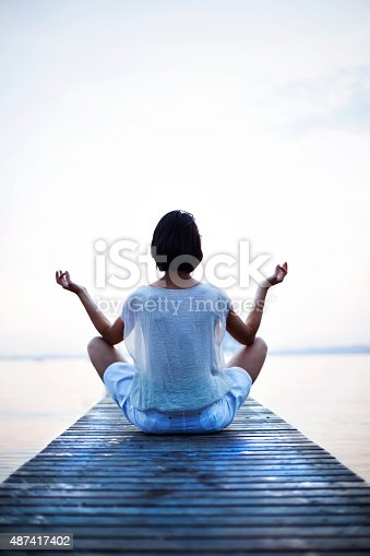 istock woman making yoga in front of the sea 487417402