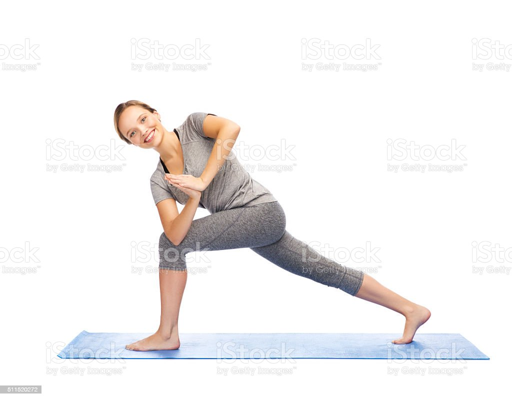 woman making yoga low angle lunge pose on mat stock photo