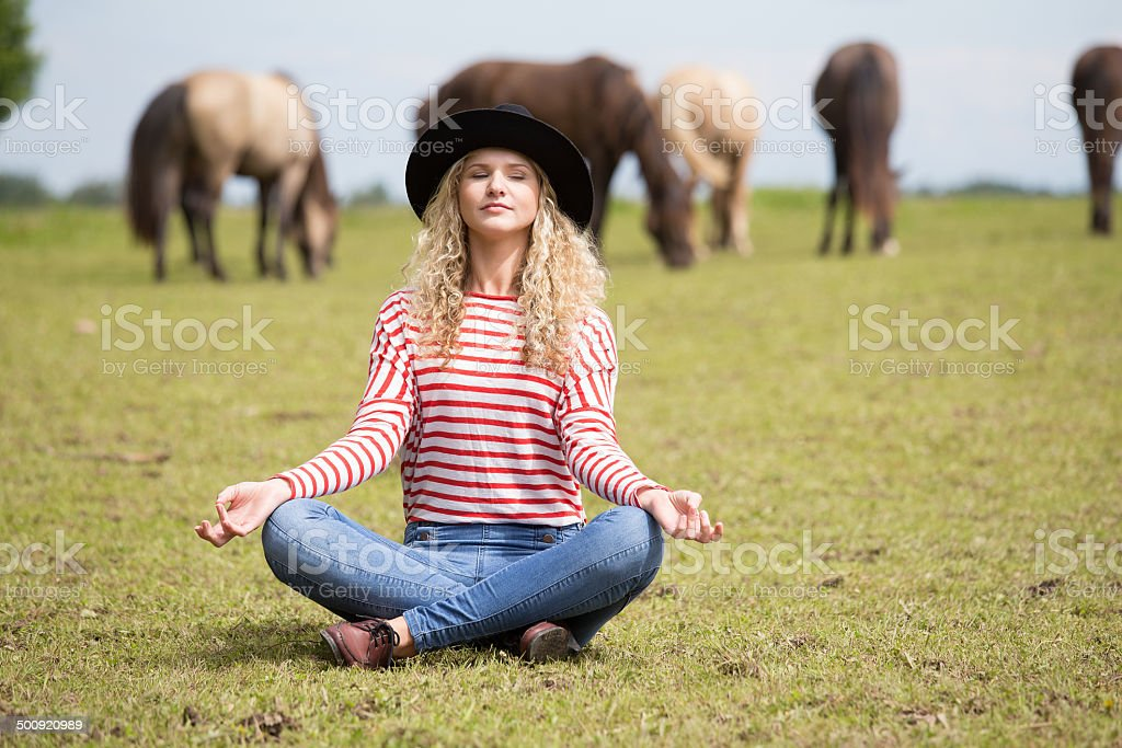 Woman making yoga on horse meadow stock photo