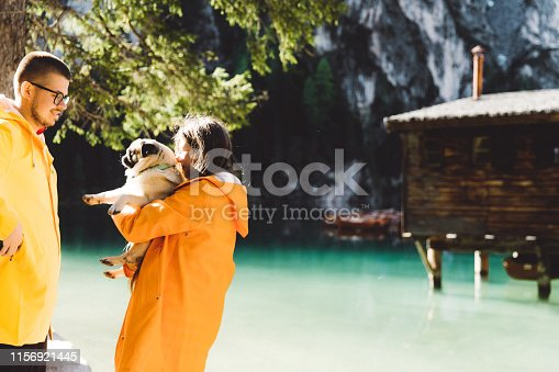 Happy woman, manned a small fluffy pug  in orange and yellow raincoats hugging near mountain hut, turquoise lake, boats and mountains in South Tyrol, Italy
