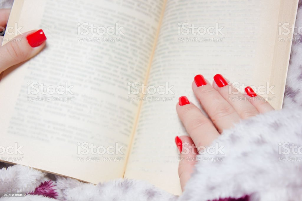 woman manicured hand with red nails and book stock photo