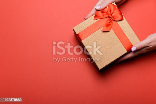 Woman manicured hands holding red and golden wrapped present or giftbox on deep red background, copy space, top view. Flat lay, giving presents concept. Background for Valentine's Day, Mother's Day.