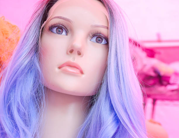Woman mannequin head in wig shop wearing blue wig.Cold and emotionless face,with eyes looking into void.Pink background,color matching vibrant pastels.Emptiness of modern world. stock photo