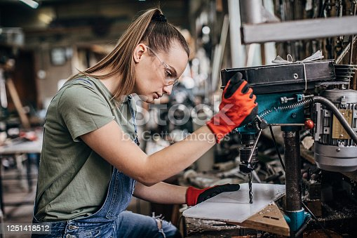 One woman, female manual worker working in workshop alone.