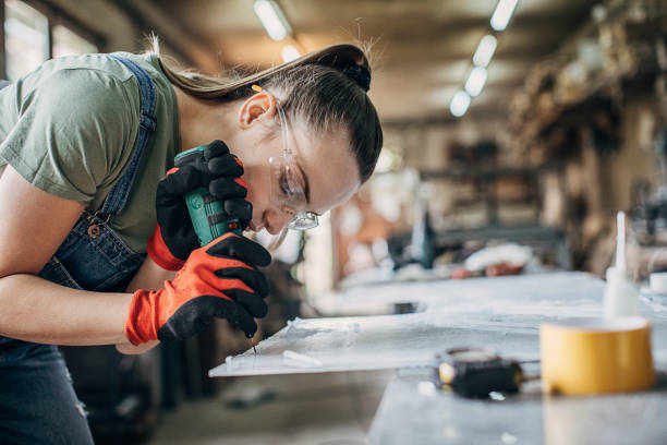 Woman manual worker working in workshop stock photo