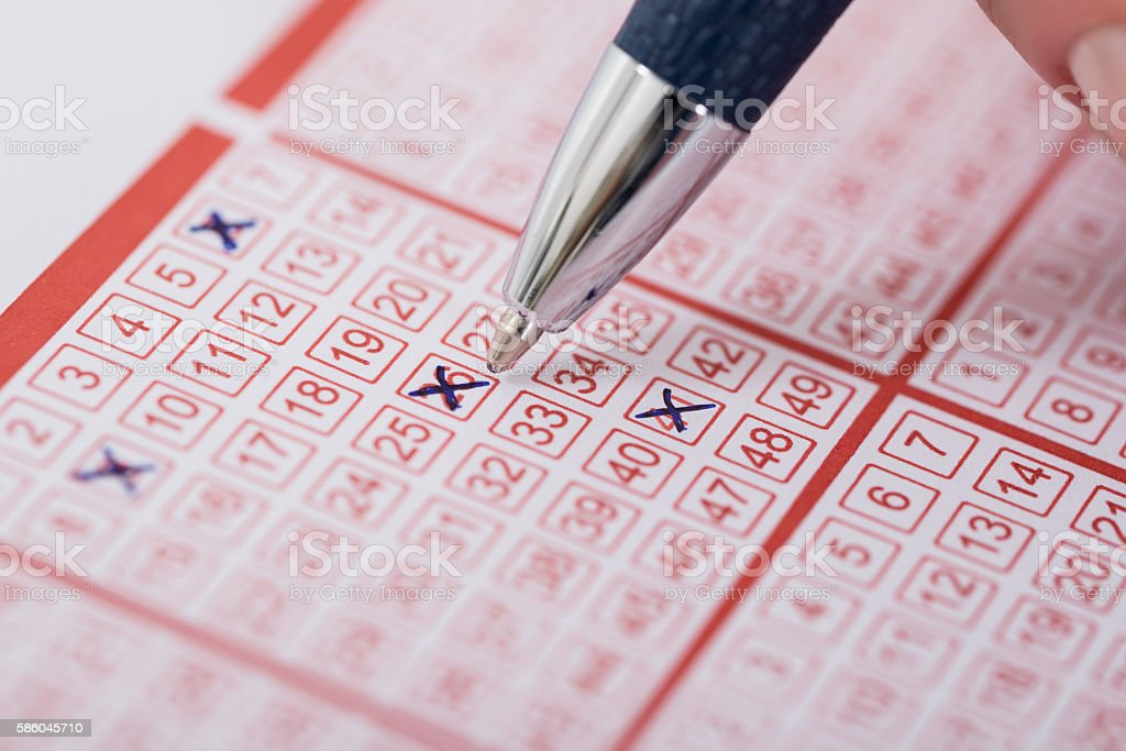 Woman Marking Number On Lottery Ticket With Pen stock photo