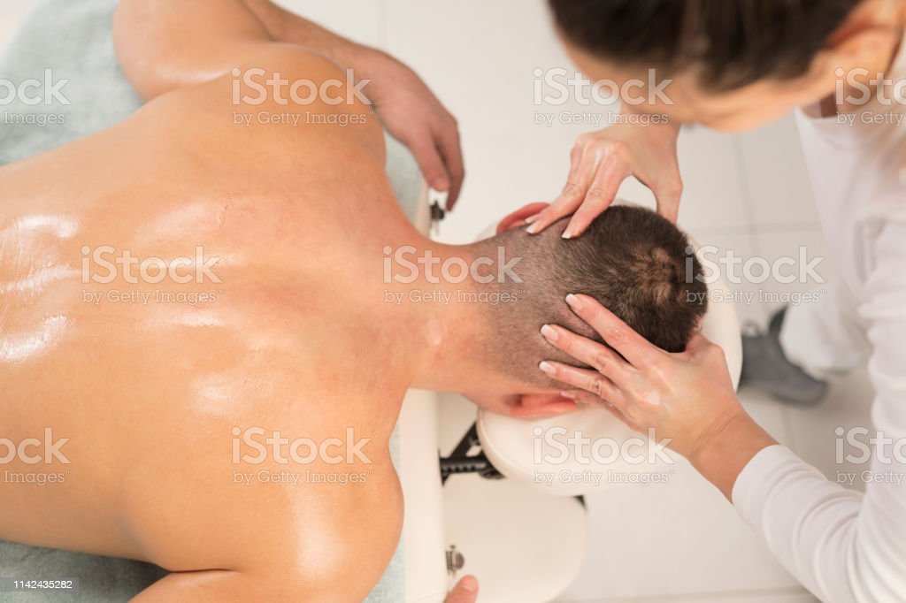 Woman Massage Therapist doing healing head massage. Men enjoying in...