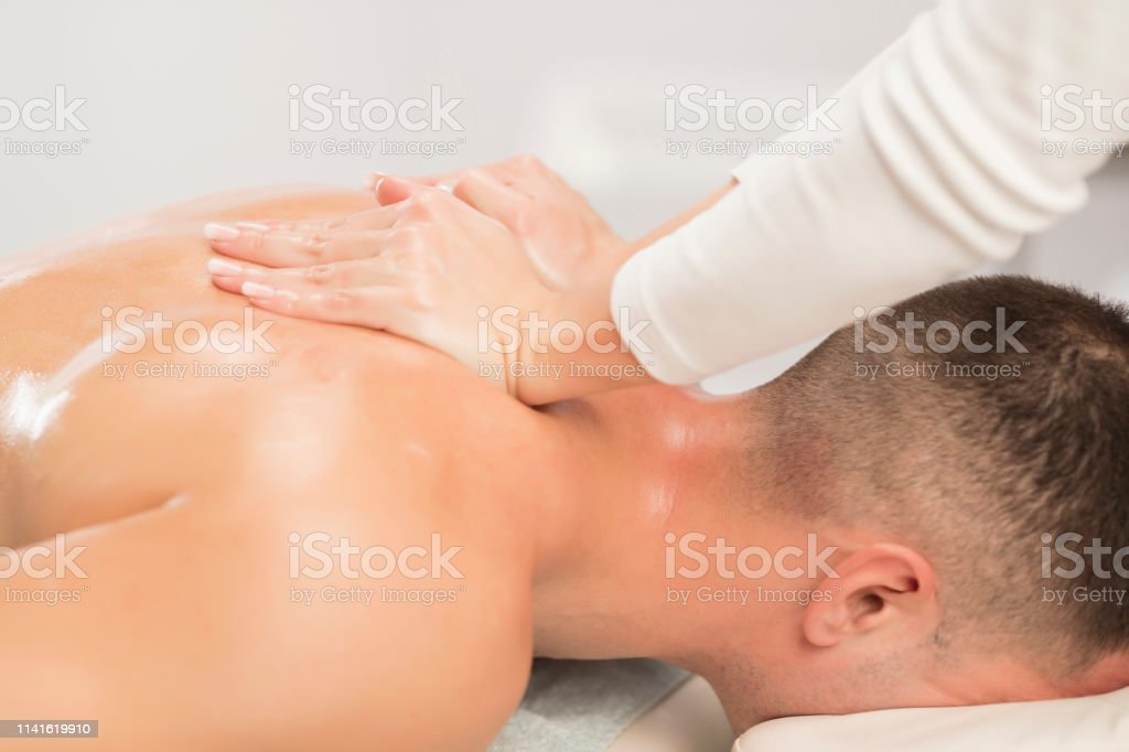 Woman Massage Therapist doing healing massage. Men enjoying in...
