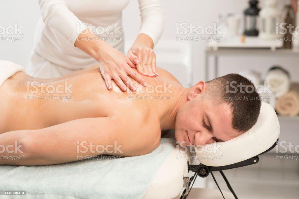 Woman Massage Therapist doing healing massage. Men enjoying in...