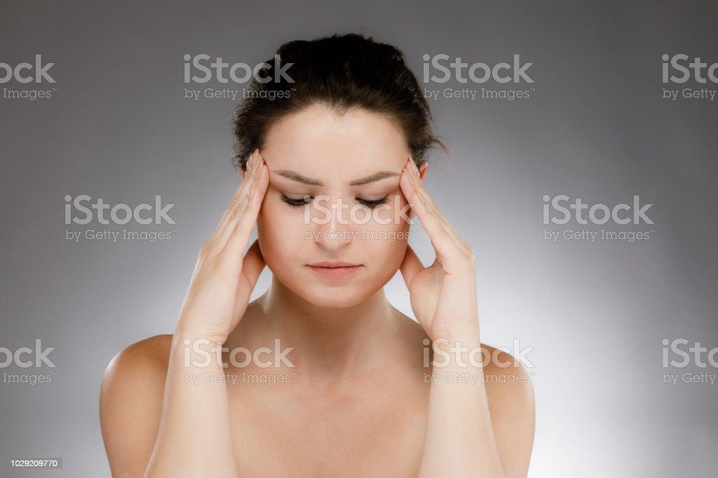 Woman massaging head pain on gray background