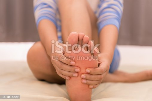 901404510istockphoto Woman massaging her foots on the bed after exercise 921814482