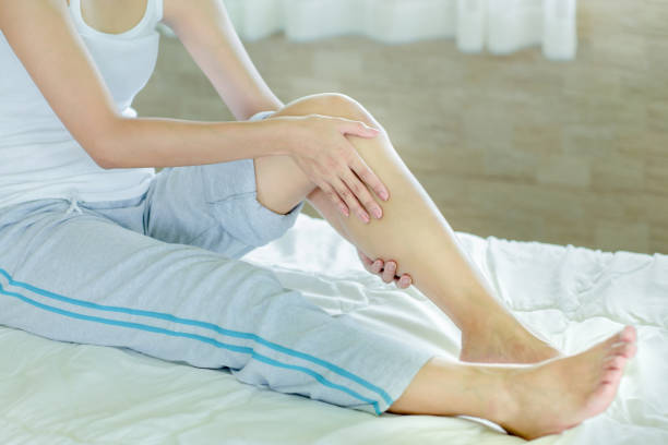 woman massaging her leg woman massaging her leg on white bed leg stock pictures, royalty-free photos & images