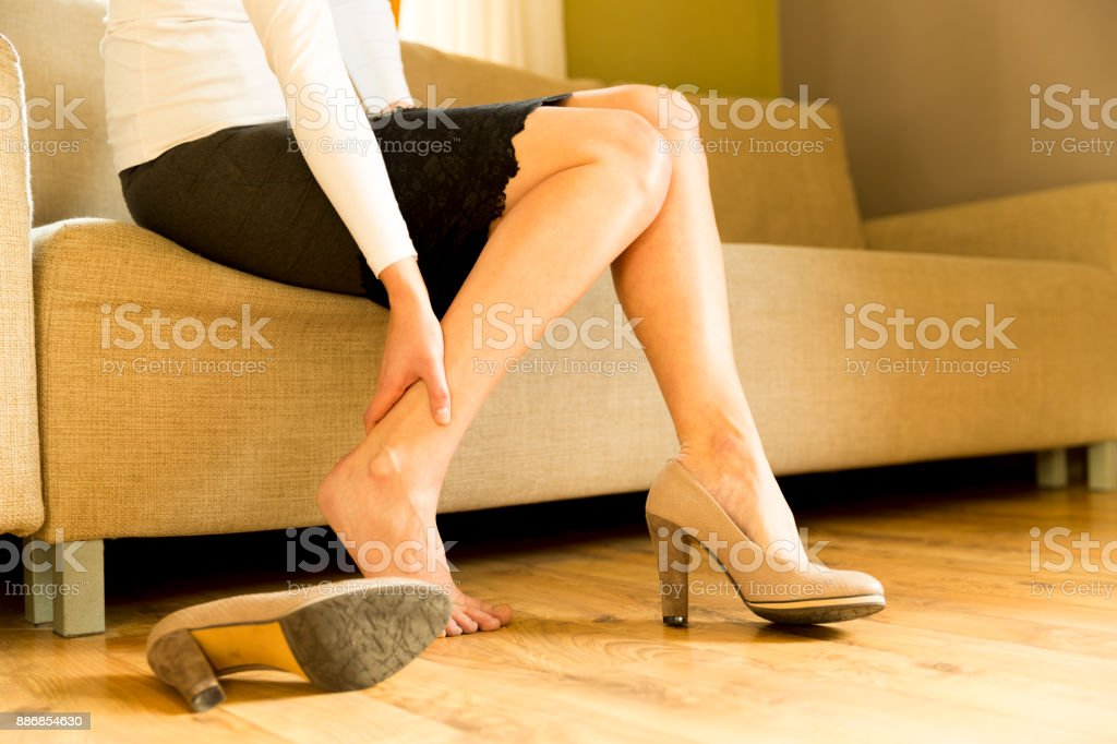 Woman massaging her legs after wearing high heels all day at work in office stock photo