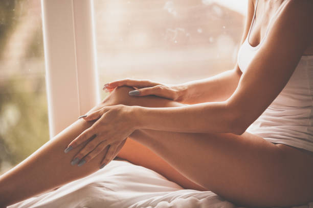 frau massiert beine zu hause - bein tag routine stock-fotos und bilder