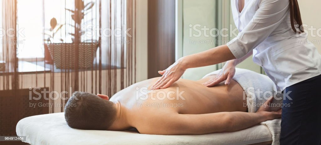 Woman massaging male shoulders and back royalty-free stock photo