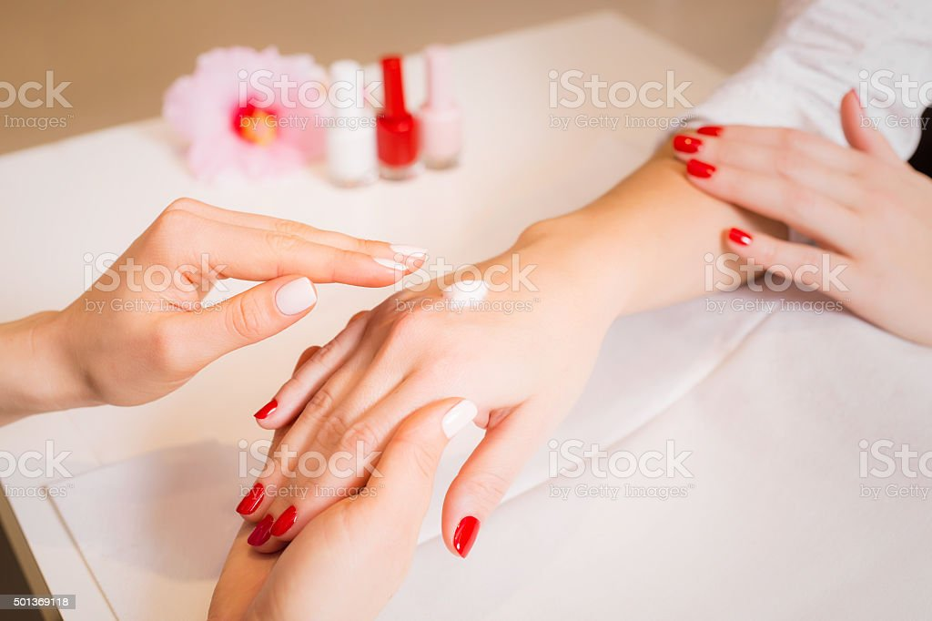 Woman massaging woman's hands after manicure stock photo