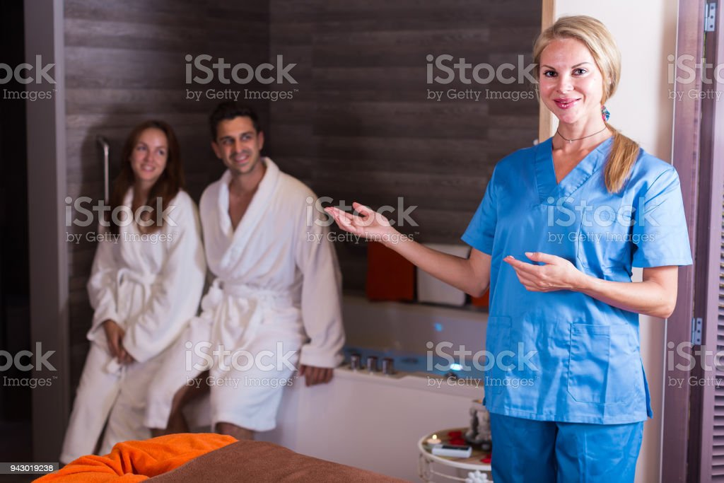 Woman massagist is ready for meet couple in massage cabinet stock photo