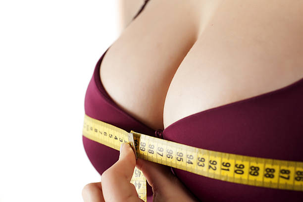 woman measured her breast with a measuring tape ストックフォト