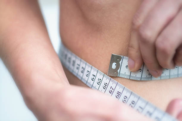 Woman measures very thin waist with measuring tape anorexia anorexia nervosa stock pictures, royalty-free photos & images