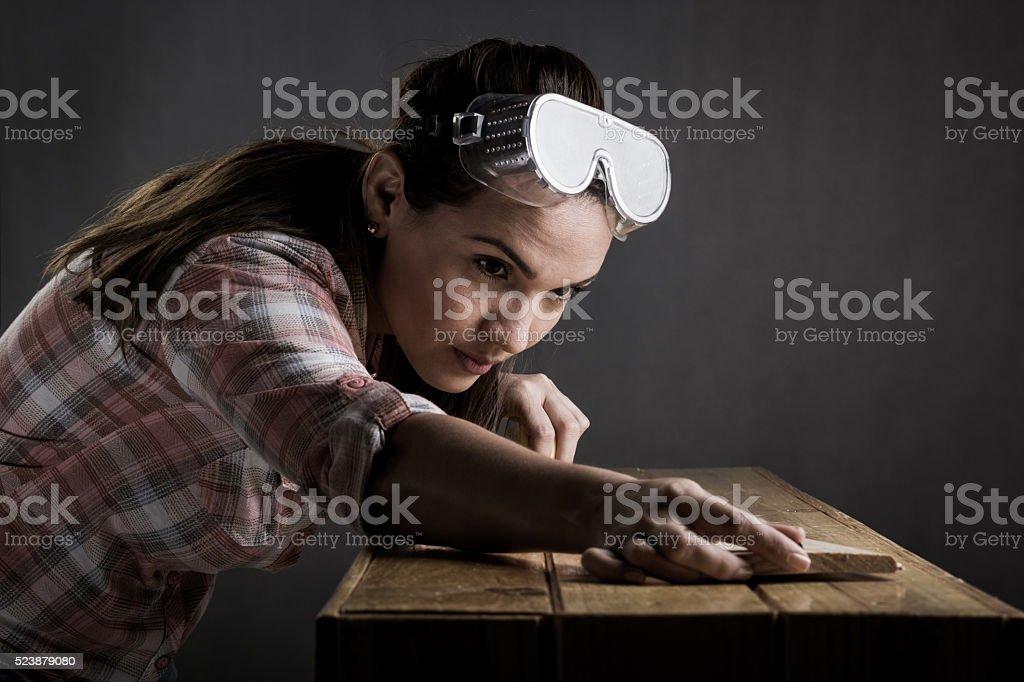 Femme mesurant un tableau en bois avec un ruban à mesurer - Photo
