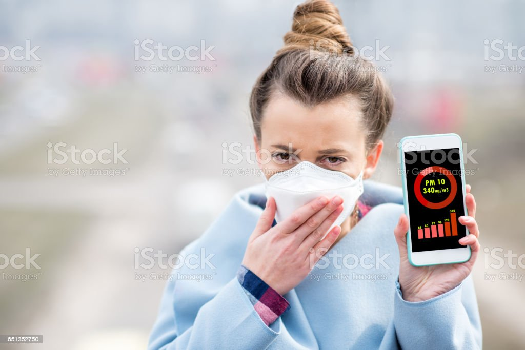 Woman measuring airpolution stock photo