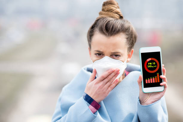 Woman measuring airpolution Woman in protective mask holding smart phone with air polution measurement of PM10 outdoors smog stock pictures, royalty-free photos & images