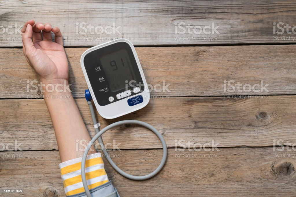 woman measuring blood pressure and pulse while nervous stock photo