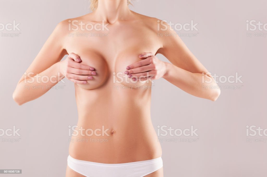 Woman measuring breast volume on gray background, perfect female body. the concept of plastic surgery stock photo