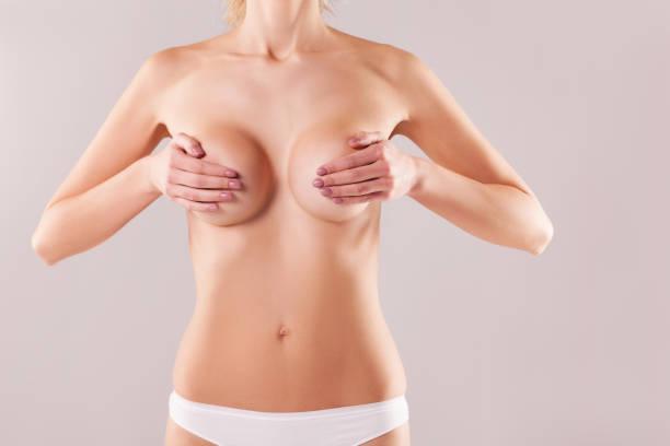 woman measuring breast volume on gray background, perfect female body. the concept of plastic surgery - seno foto e immagini stock