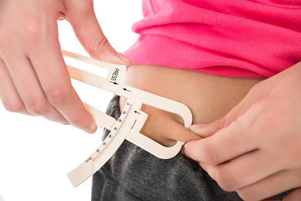 Woman Measuring Fats With Caliper - foto de acervo