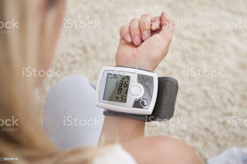 Woman measuring her blood pressure royalty-free stock photo